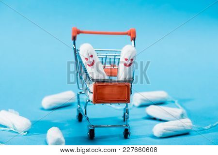 Tampons With Happy Smileys In Small Shopping Cart On Blue