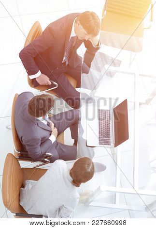 Three business people, meeting around a boardroom table
