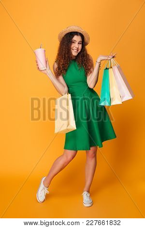 Photo of happy young woman standing isolated over yellow background. Looking camera drinking aerated water holding shopping bags.