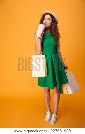 Photo of amazing young woman standing isolated over yellow background. Looking aside drinking aerated water holding shopping bags.