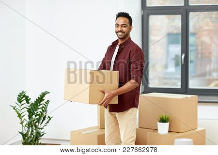 moving, people and real estate concept - happy indian man with boxes at new home