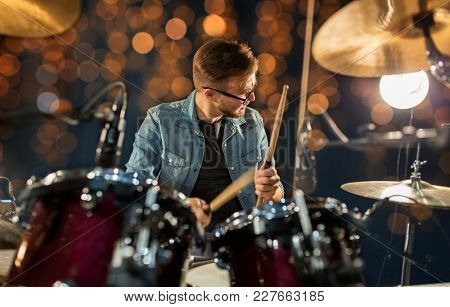 music, musical instruments and entertainment concept - male musician with drumsticks playing drums and cymbals at concert or studio over holidays lights background