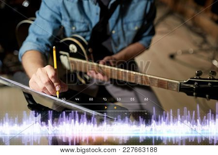 people and entertainment concept - man with guitar writing notes to music book at sound recording studio