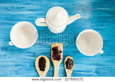 Top View On Tea Cups Next To Wooden Spoons With Tea Leaves On Vintage Blue Background