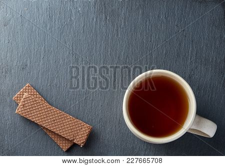 White Ceramic Porcelain Cup Of Tea With Stack Of Chocolate Cookies On Dark Background, Top View. Ple