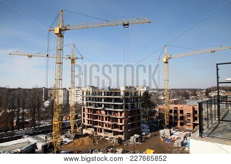 Working Crane On The Construction Of The House. Construction Site With Cranes On Sky Background.