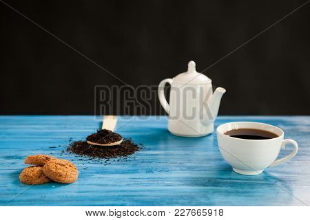 Hot Tea Next To A Spoon With Tea Leaves On Vintage Blue Board Over Black Background