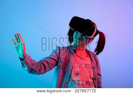 Happy Young Girl Touching A Virtual Button Wearing A Vr Headset