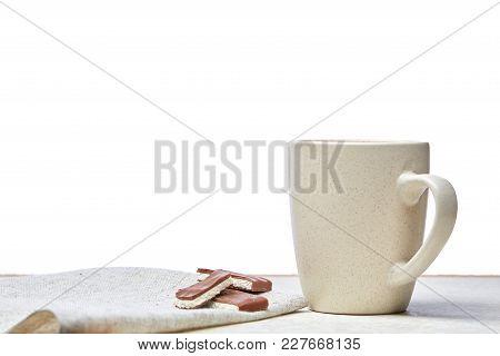 White Ceramic Porcelain Coffeecup With A Couple Of Chocolate Pieces On White Cotton Napkin On Light