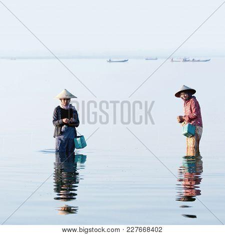 Amarapura, Myanmar - January 12, 2011: Burmese Girls Catching Fish For Food On Taungthaman Lake In M