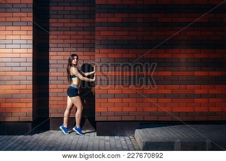 An Attractive Young Woman In Sportswear Posing Against A Brick Wall Background With Copyspace. Train