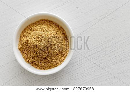 Finely Ground Dry Ginger In White Ceramic Bowl Isolated On White Wood Background From Above.