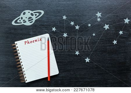 Zodiacal Star, Constellations Phoenix On A Black Background With A Notepad And Pencil.