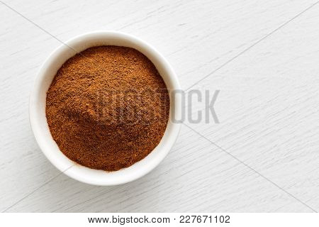 Finely Ground Cinnamon In White Ceramic Bowl Isolated On White Wood Background From Above.