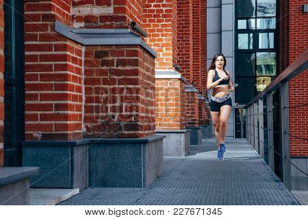 Woman Running At Outdoor On A Background Of Cityscape