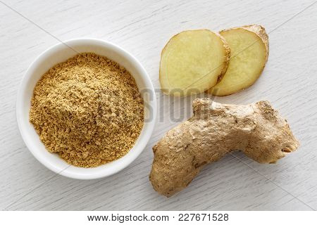 Finely Ground Dry Ginger In White Ceramic Bowl Isolated On White Wood Background From Above. Fresh W