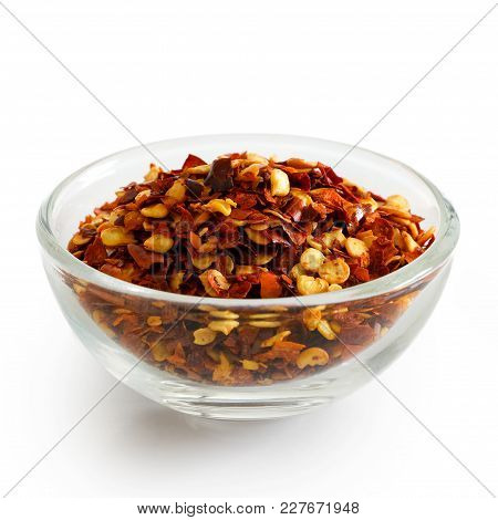 Coarsely Ground Chilli Peppers In Glass Bowl Isolated On White.