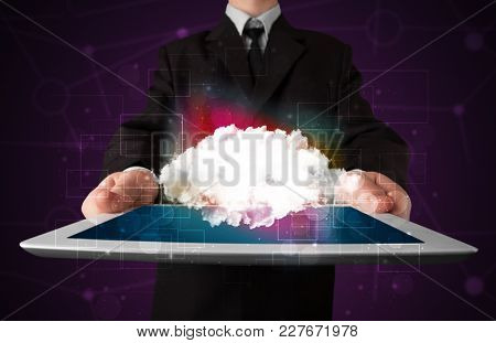 Businessman holding tablet with cloud icon and purple background