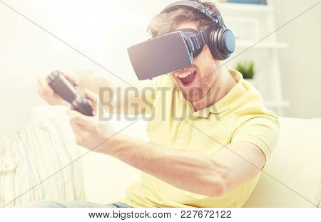 technology, gaming, entertainment and people concept - happy young man with virtual reality headset or 3d glasses with controller gamepad playing racing video game at home
