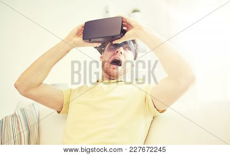 3d technology, virtual reality, gaming, entertainment and people concept - scared young man taking off virtual reality headset or 3d glasses while playing game