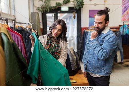 sale, shopping, fashion and people concept - happy couple choosing clothes at vintage clothing store
