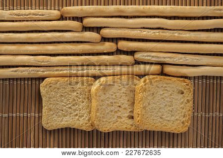 Rows Of Breadsticks And Toasts On A Wicker Mat
