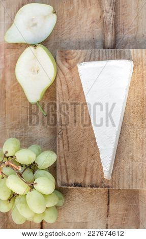 Fresh Brie Cheese  On Cutting Board With Grapes And Fruits, Top View. Brie Cheese  On White  Rustic