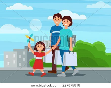 Happy Family Walking By Park After Shopping. Mother, Father And Their Little Daughter. City Building