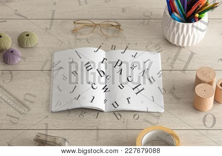 Open notebook on the floor with office instruments nearby and letters on it