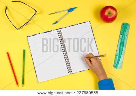 Colorful School Workspace. Kid Hand With Open Notebook, Pen, Ruler, Glasses And Fresh Apple On Yello