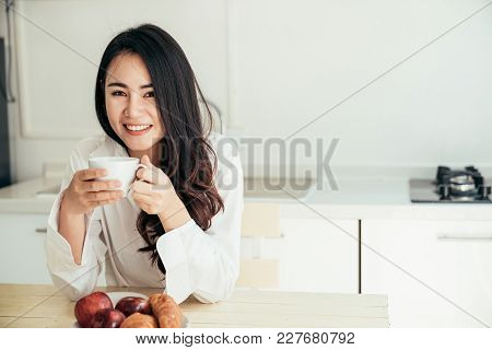 Asian Girl Who Just Wake Up In The Morning As Relaxed. She Opened The Window To Receive The Light Of