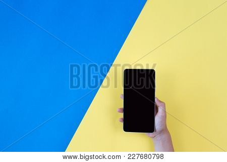 Hand Holding The Phone On Blue And Yellow Background. Top View