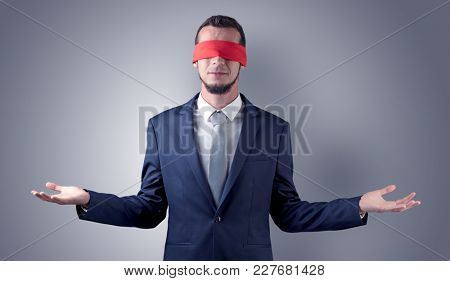 Covered eye, indecisive businessman standing blind in front of a wall