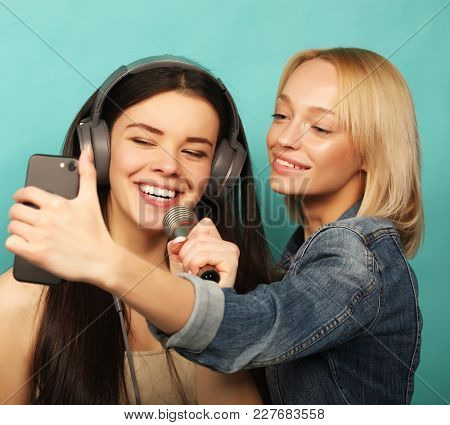 lifestyle, emotion  and people concept: Happy young girls  with microphone  take picture with smartphone over blue  background