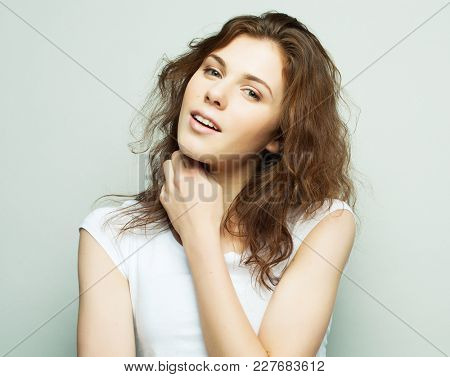 lifestyle, fashion and people concept: young curly woman posing in studio, casual style, teenager.