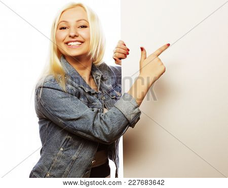 Gorgeous blond woman pointing at a board while standing against a white background