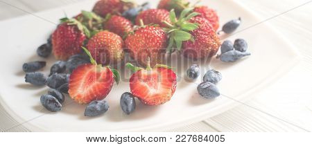 Close-up Of A Scattering Of Fresh Berries Of Strawberry And Honeysuckle On A Dark Wooden Boards