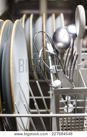 Clean cutlery in the dishwasher. Home equipment. Work at home concept