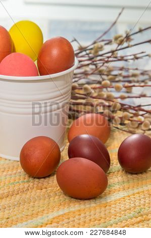 Easter Eggs In A Bed Of Straw In A White Bucket, Five Other Eggs In Front Of A Bucket In The Backgro