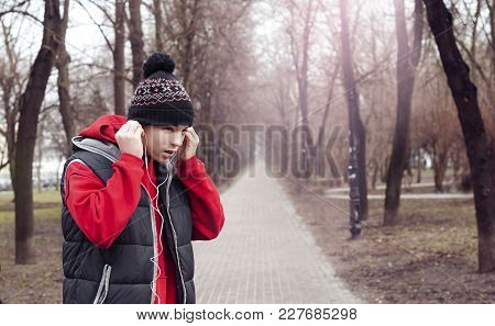 Sporty Young Man Listening To Music In City Park