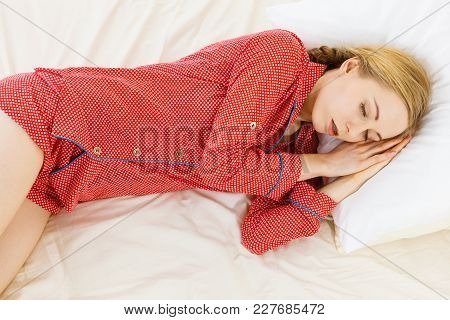 Relax Rest Sleep Positions Concept. Girl Drowning In Dreams. Young Woman Wearing Red Dotted Pajamas