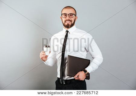 Image of working businessman in glasses and suit holding takeaway coffee and laptop in hands isolated over gray background