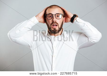 Image of confused or shocked adult man in white shirt and eyeglasses grabbing his head isolated over gray background