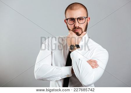 Image of concentrated adult man in business outfit touching his chin and posing with brooding look isolated over gray background