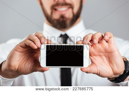 Close up of a happy businessman showing blank screen mobile phone isolated over gray background