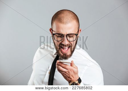 Portrait of a mad businessman yelling at mobile phone isolated over gray background