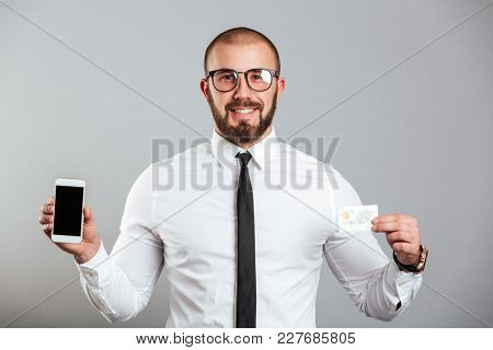 Photo of happy successful man in glasses and tie holding cell phone and credit card isolated over gray background