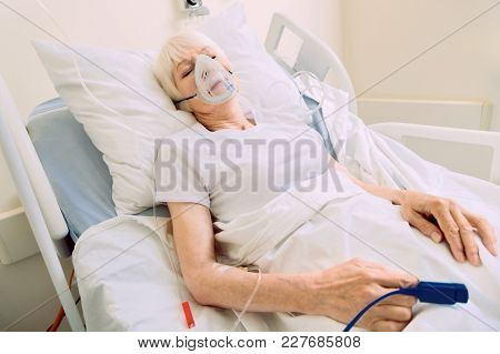 Serious Health Problem. Poor Elderly Woman Lying In A Hospital Bed With A Pulse Oximeter And A Drop
