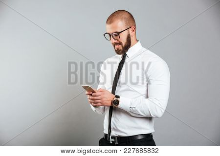 Photo of happy successful man in glasses and tie communicating while holding smartphone in hands isolated over gray background