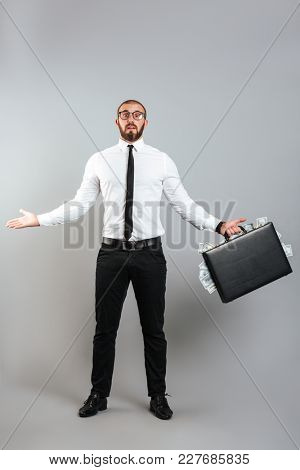 Image of puzzled man entrepreneur in glasses and business suit throwing up hands with diplomat full of dollar money isolated over gray background